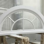 Curved timber window painted white
