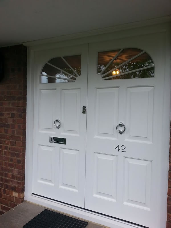 Double entrance door with custom arched windows