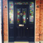 Black entrance door with stained decorative glass